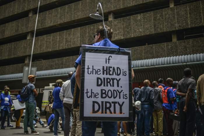 "A political demonstrator mocks Zuma's ""shower"" comments"