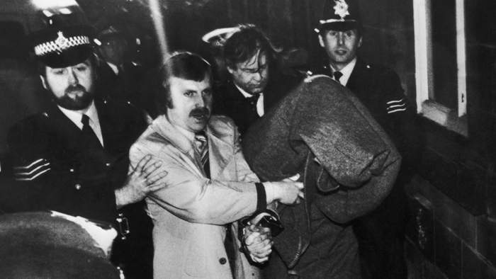 His head covered with a blanket, Peter Sutcliffe, is escorted into Dewsbury Magistrates Court to be charged with murder, 6 January 1981