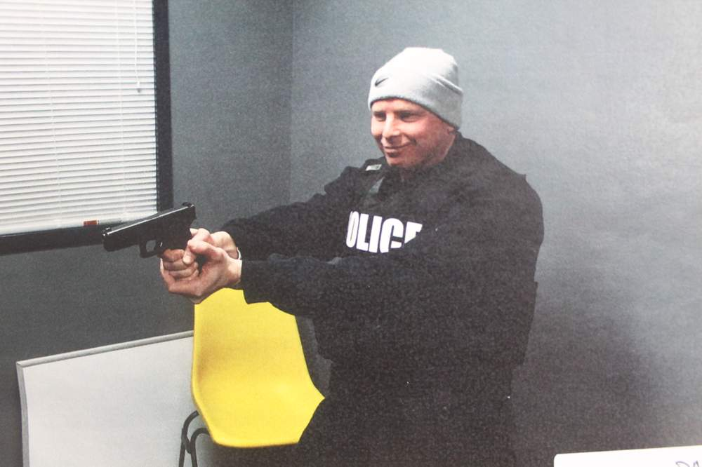 Stepp wears Jenkins' vest and holds his gun at BPD headquarters.