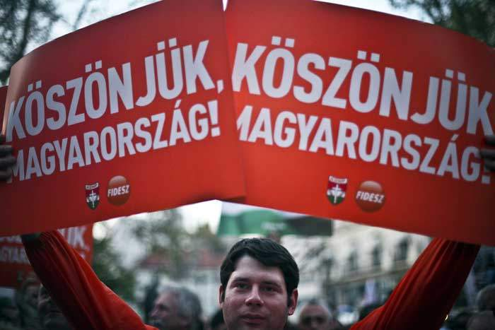"""2010: A Fidesz supporter carries a banner reading """"Thank you Hungary"""""""