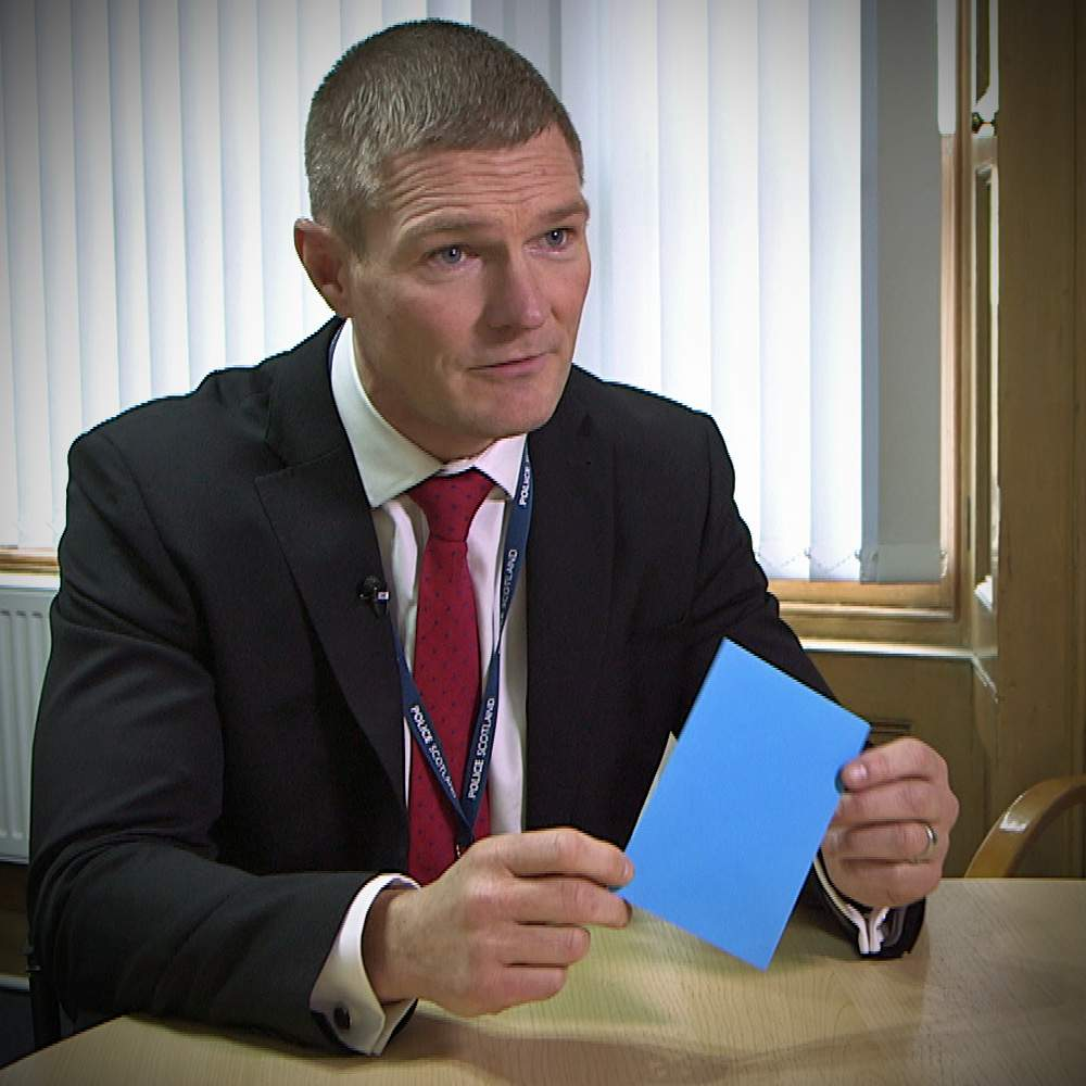 Det Supt Gary Cunningham, of Police Scotland's Major Investigation Team, holds an envelope similar to the one handed to Alistair Wilson