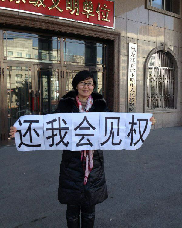 Wang Yu holds a sign asking for her rights to be honoured, January 2015