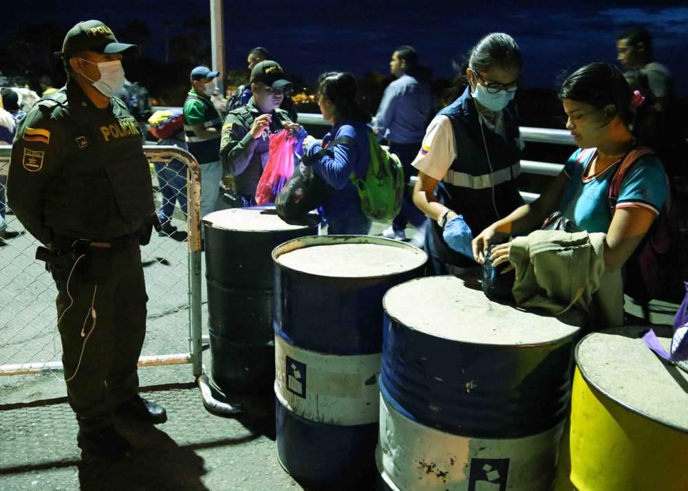 Venezolanos pasan a través de un punto migratorio.