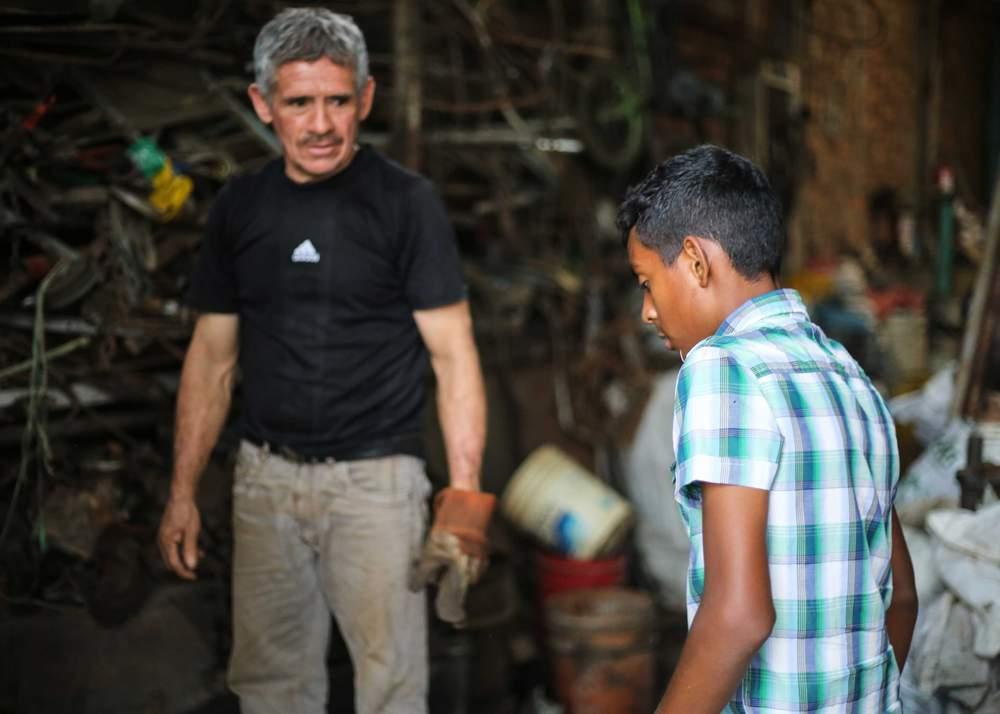 Pompilio Rincón en su local de chatarra con un recolector, Breiner Hernández