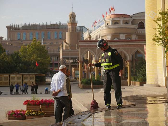 رجل شرطة ينظف درجات مسجد كاشغار