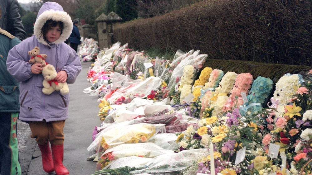 A child lays teddy bears at a memorial in Dunblane in 1996 (Picture: Getty Images)