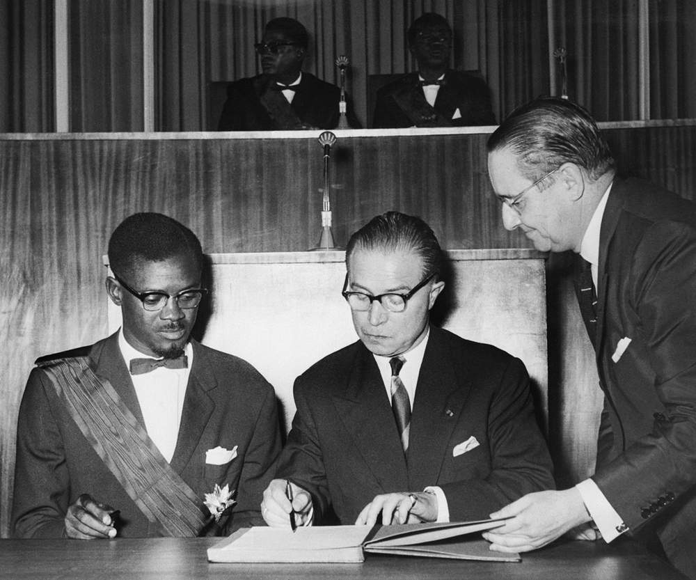 Prime Minister Patrice Lumumba (l) and Belgian Prime Minister Gaston Eyskens sign the act of independence, 1960