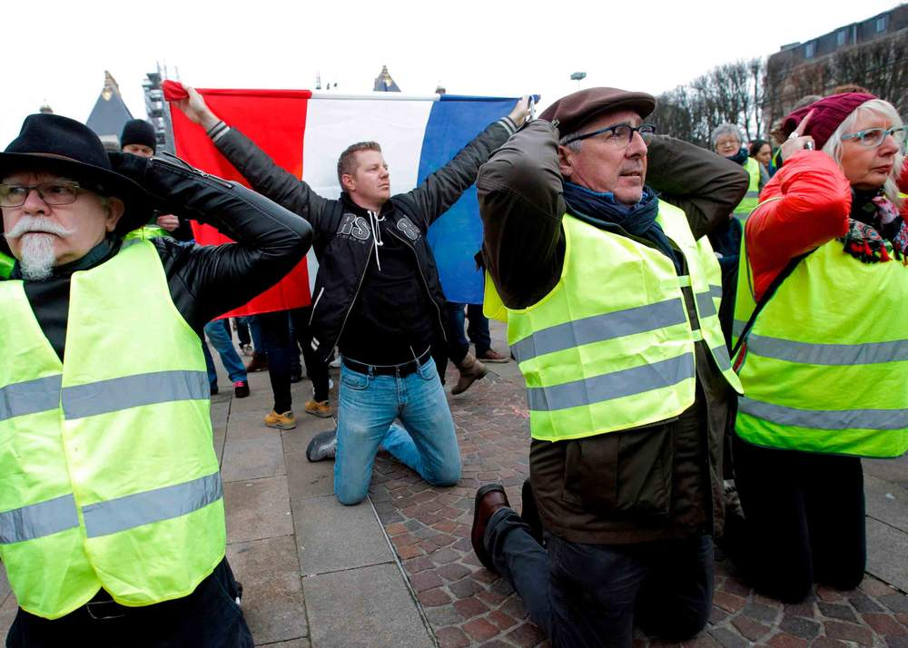 Protesters demonstrate on their knees against rising costs of living in Lille