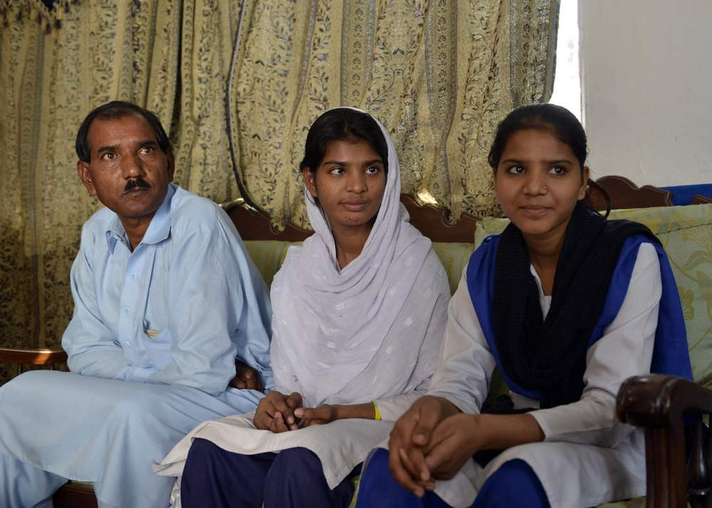 Asia's husband Ashiq Masih (L) sits with daughters Esham (R) and Esha (C)