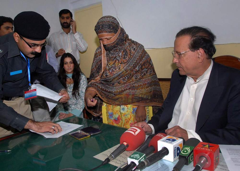 A police official takes the thumb print of Asia Bibi (C) during a visit from Governor Salman Taseer (R) at the central jail in Sheikhupura