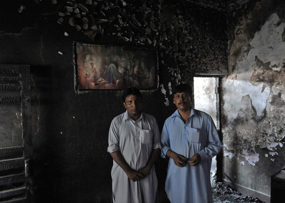 Two Pakistani Christians stand in their burnt-out house in Gojra, 2009