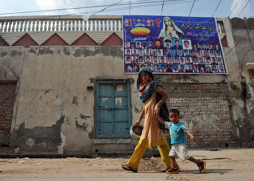 A woman walks with her child in Gojra