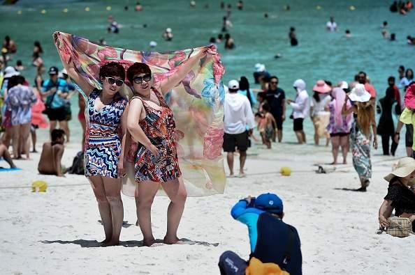 Guia tira foto de turistas na praia de Maya Bay antes do fechamento