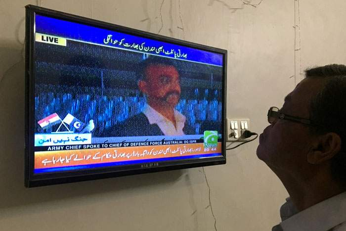 A man watches the televised release of Indian Wing Cdr Abhinandan