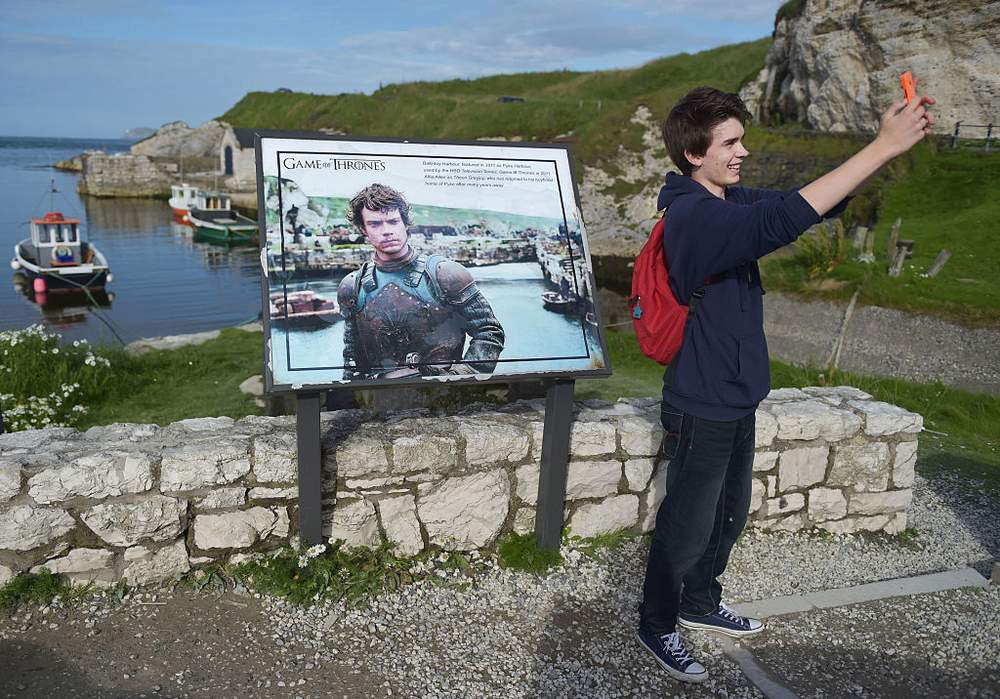 A fan takes a picture at the Game of Thrones plaquein Ballintoy Harbour, County Antrim