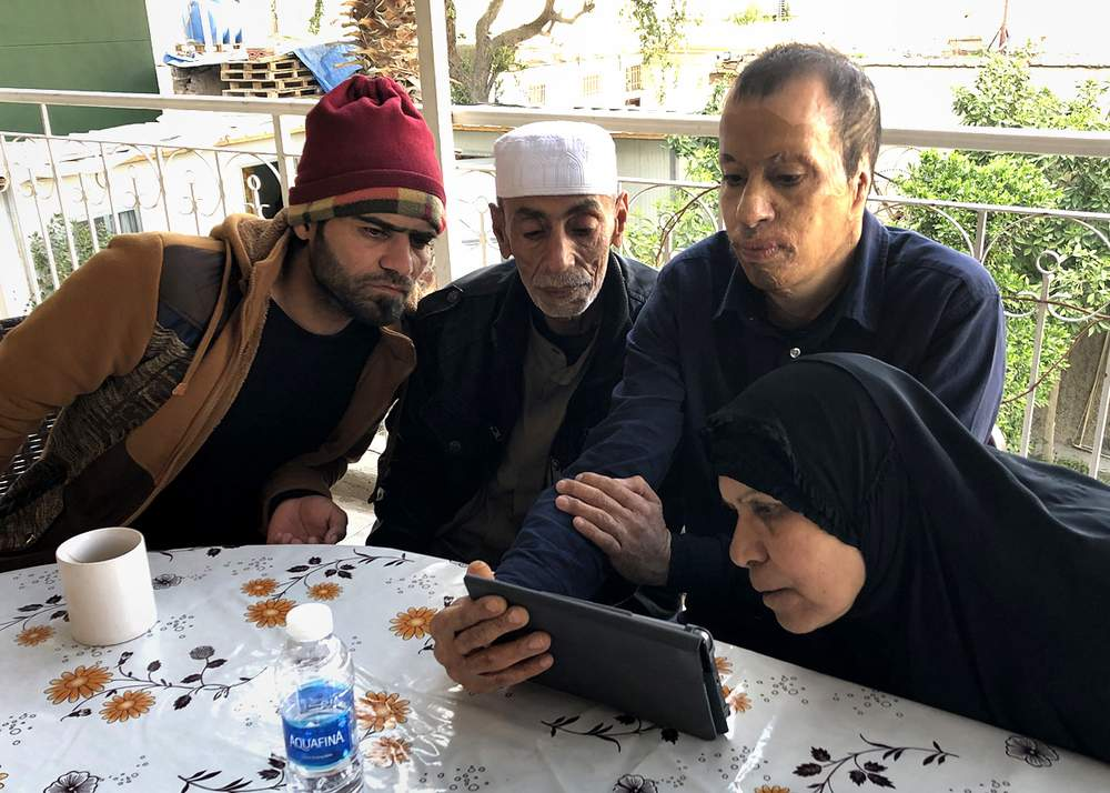 Tahrir, Juma, Amar and Zahra look at photos on Amar's tablet