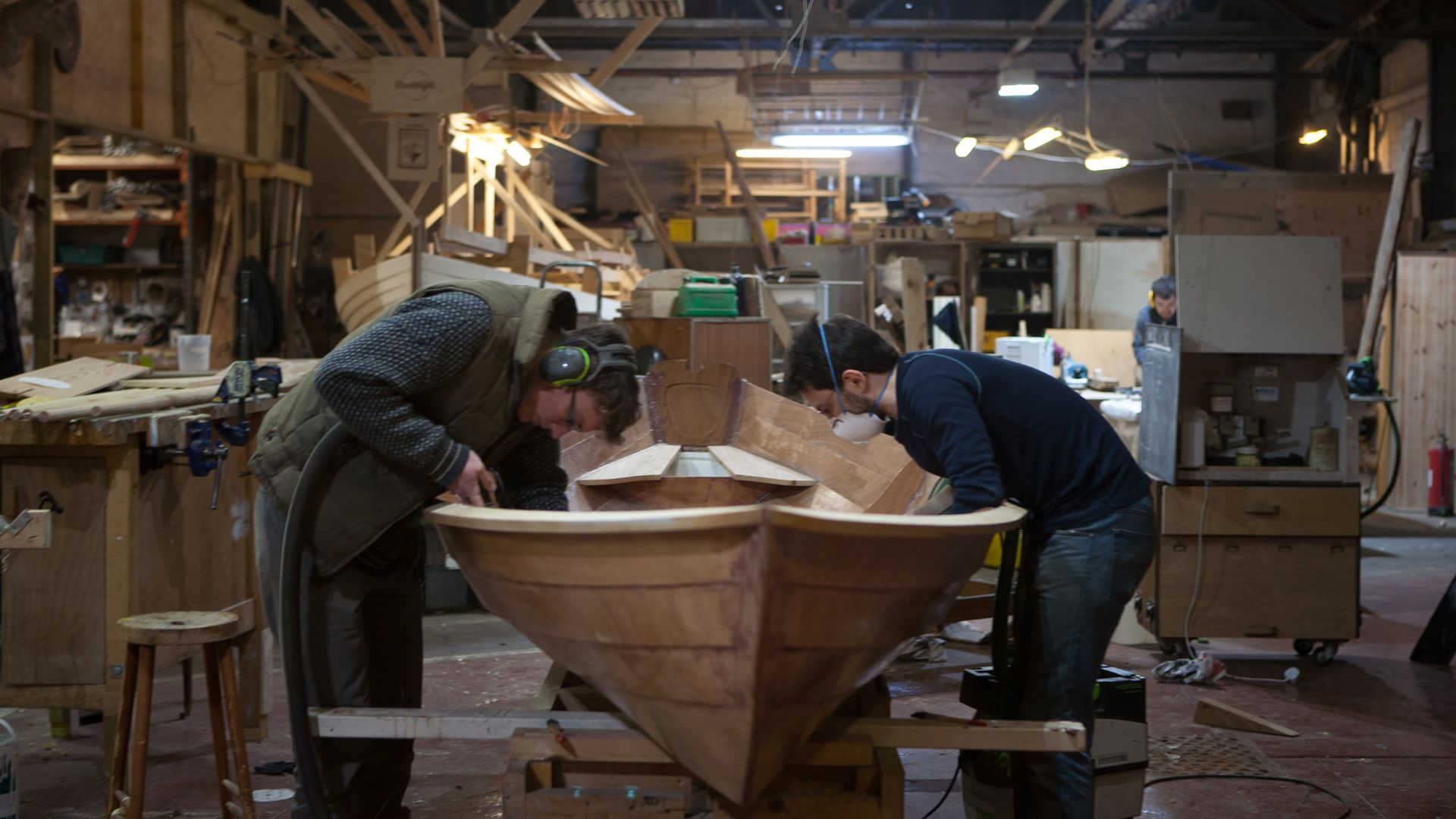 Two men working on a boat in the workshop