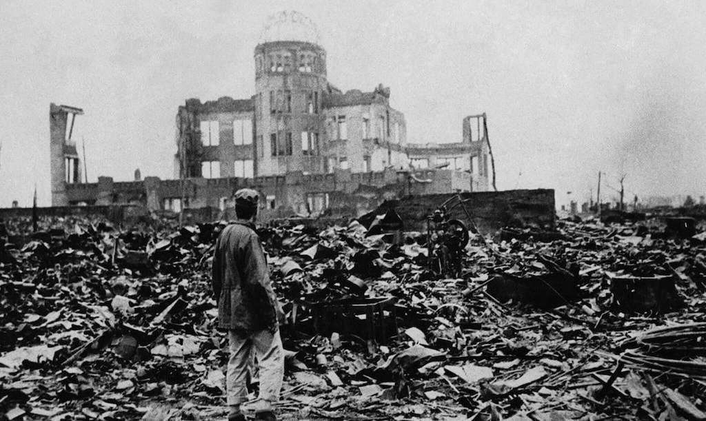 Un hombre parado ante un edificio destruido en Hiroshima