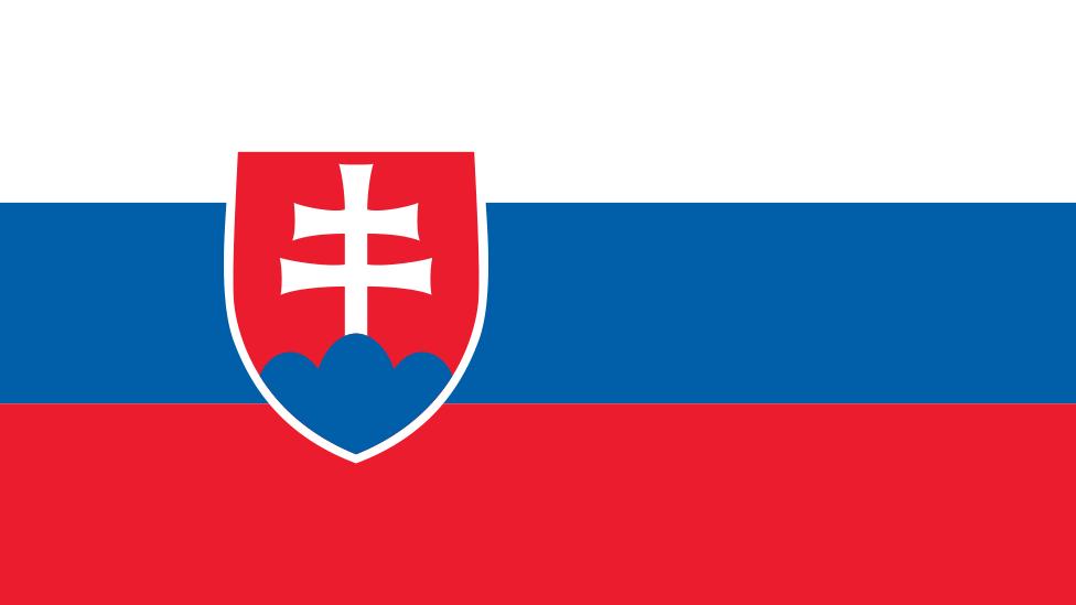 Bandera de Eslovaquia (de arriba a abajo) blanco, azul y rojo, con un escucho a la izquierda que muestra una cruz blancasobre un fondo rojo.