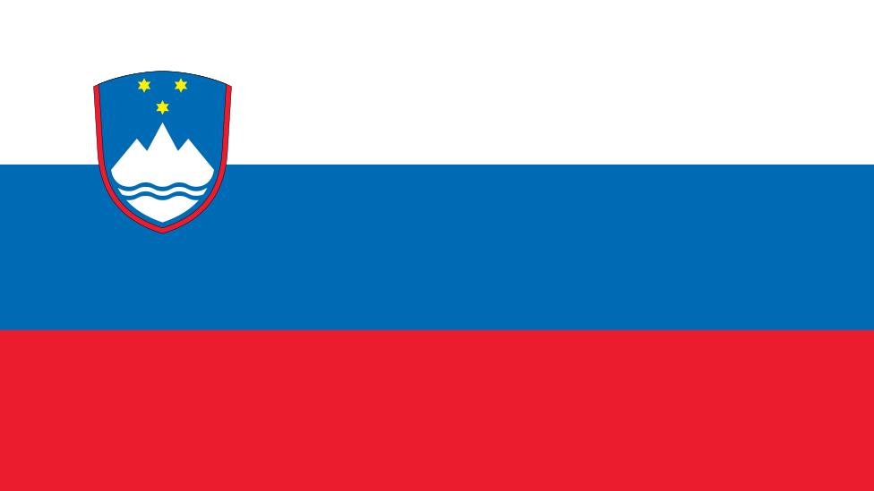 Bandera de Eslovenia (de arriba a abajo) blanco, azul y rojo, con un escudo a la izquierda que muestra una montaña blanca coronada con tres estrellas amarillas.